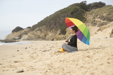 Woman with colorful umbrella sitting on the beach - KBF00560
