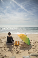 Woman with colorful umbrella sitting on the beach, rear view - KBF00563