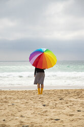 Woman with colorful umbrella sitting on the beach - KBF00566