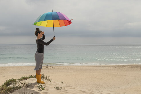 Woman with colorful umbrella sitting on the beach - KBF00569