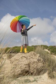 Woman with colorful umbrella standing on a rock and looking at distance - KBF00572
