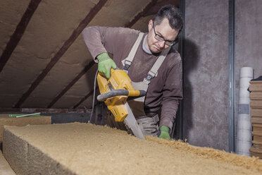 Roof insulation, worker placing wood fibre insulation at the roof - SEBF00027