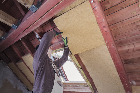 Roof insulation, worker placing insulating board, wood fibre - SEBF00033