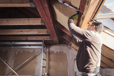 Roof insulation, worker filling pitched roof with wood fibre insulation - SEBF00036