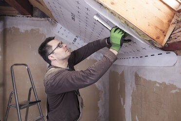 Roof insulation, worker fixing sarking membrane - SEBF00039