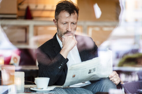 Portrait of pensive mature businessman reading newspaper in a coffee shop - DIGF06001