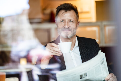 Portrait of smiling mature businessman with newspaper in a coffee shop drinking coffee - DIGF06004