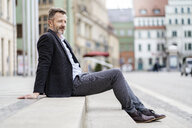 Germany, Zwickau, relaxed mature businessman sitting on steps outdoors - DIGF06007