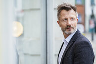Portrait of mature businessman with greying beard watching something - DIGF06013