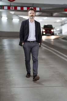 Portrait of mature businessman walking at underground car park - DIGF06028