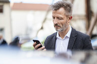 Portrait of mature businessman looking at cell phone - DIGF06031