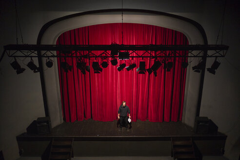 Actor with script standing on theatre stage in front of red curtain - FBAF00250
