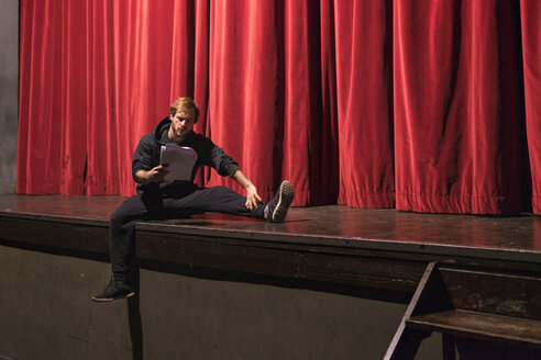 Actor sitting on stage of theatre studying script - FBAF00268