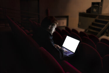 Director sitting at auditorium of theatre working on laptop - FBAF00283