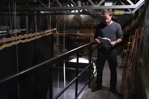 Actor at theatre studying script backstage - FBAF00298