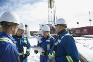 Workers talking snow below drilling rig gas plant - HEROF27029