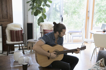 Young man playing guitar in living room - HEROF27113