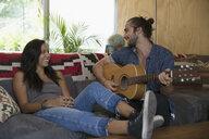 Young couple playing guitar on living room sofa - HEROF27116