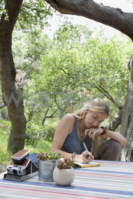 Young woman writing in journal at patio table - HEROF27125