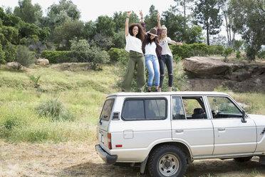 Young women dancing on top of car - HEROF27128