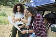 Young women looking at map at back of car - HEROF27131