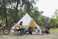 Young friends relaxing playing guitar outside camping yurt - HEROF27146