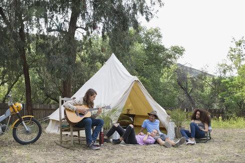 Young friends relaxing playing guitar outside camping yurt - HEROF27146