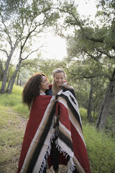Young women hugging wrapped in a blanket in woods - HEROF27155