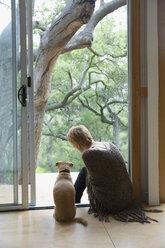 Woman and dog sitting in patio doorway - HEROF27158
