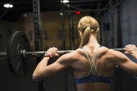 Woman weightlifting at barbell rack - HEROF27203