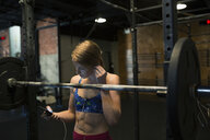 Woman with headphones and mp3 player at barbell - HEROF27206
