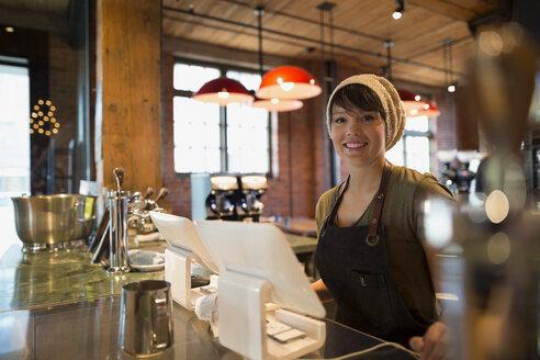 Portrait smiling barista in coffee shop - HEROF27242