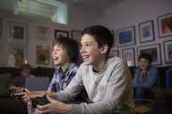 Smiling boys playing video game in living room - HEROF27284
