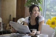 Smiling woman reading newspaper at laptop - HEROF27287