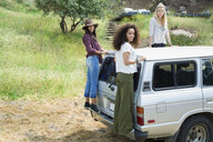 Portrait young women standing on car - HEROF27299