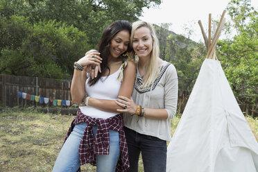 Portrait smiling women hugging outside of teepee - HEROF27302