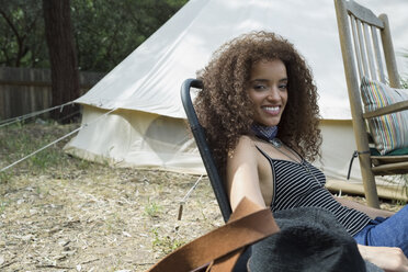 Portrait smiling young woman outside camping yurt - HEROF27305