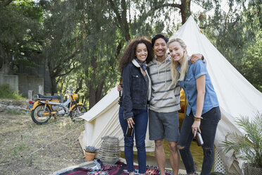 Portrait smiling young friends standing outside camping yurt - HEROF27311