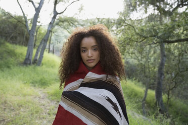 Portrait serious young woman wrapped in a blanket in woods - HEROF27314