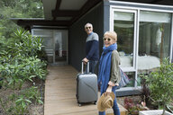 Portrait mature couple with suitcases arriving at vacation rental - HEROF27323