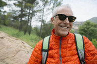 Portrait smiling mature man hiking with backpack - HEROF27326