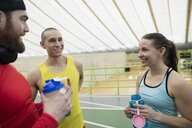 Runners resting talking drinking water on indoor track - HEROF27380