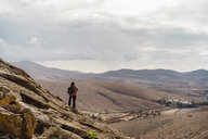 Spain, Canaray Islands, Fuerteventura, man looking at view - AFVF02562