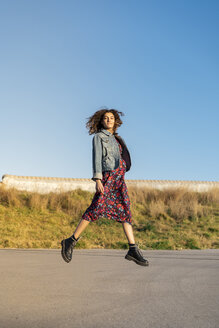 Portrait of young woman with curly brown hair jumping in the air - AFVF02568