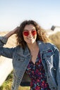 Portrait of happy young woman with curly brown hair wearing red sunglasses leaning on a wall - AFVF02571