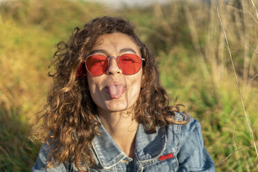 Portrait of young woman with curly brown hair wearing red sunglasses sticking out tongue - AFVF02577