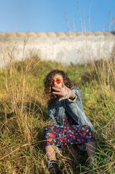 Portrait of young woman sitting on a meadow raising her hand - AFVF02580
