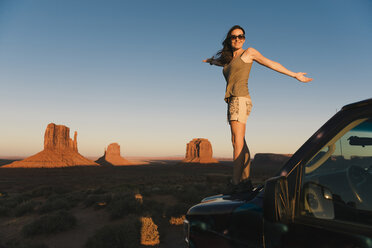 USA, Utah, Monument Valley, Woman standing on car bonnet, enjoying the sunset in Monument Valley - GEMF02867