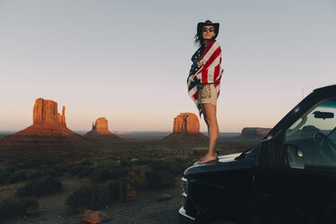 USA, Utah, Monument Valley, Woman with United States of America flag enjoying the sunset in Monument Valley - GEMF02870