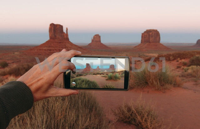 USA, Utah, Monument Valley at sunset, woman's hand taking a photo with mobile - GEMF02873 - Gemma Ferrando/Westend61